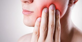 A woman in need of help from emergency dentistry services in Canning Vale